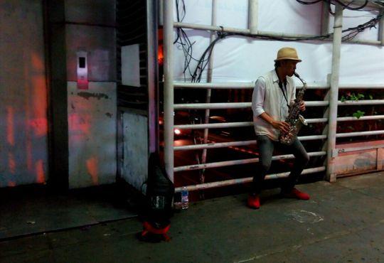 pengamen dengan saksofonnya di atas jembatan penyeberangan sarinah jakarta pusat