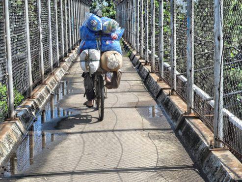 sepeda penjual kapuk terpaksa meniti jembatan penyeberangan orang di atas jalan tol JORR