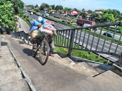 sepeda penjaja kapuk harus melalui jembatan penyeberangan di atas jalan tol JORR