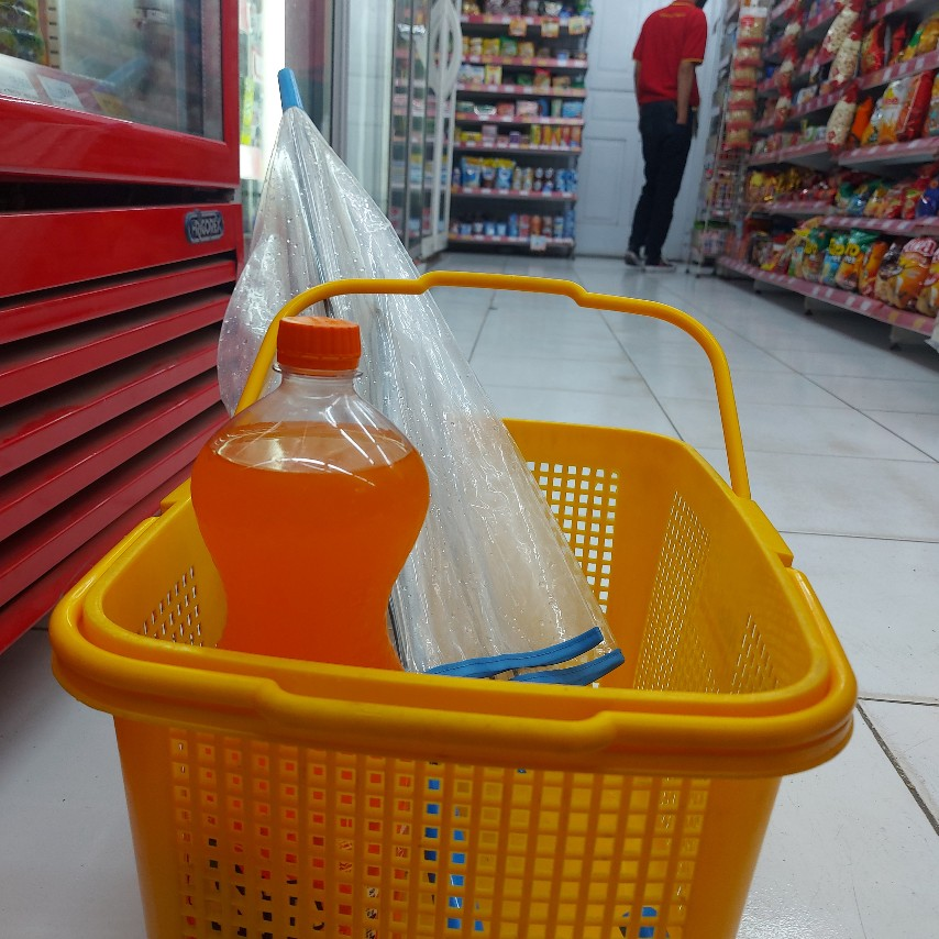 Memasukkan payung basah ke dalam keranjang belanja