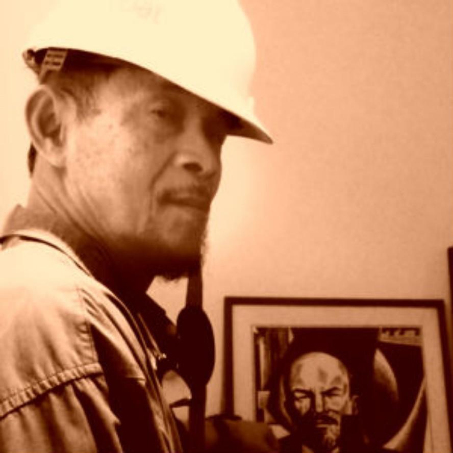Goenawan Mohamad dengan helm proyek di depan potret Lenin